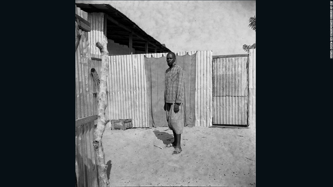 The setting and proportions mark this as a formal portrait of a man believed to be a mason in his everyday work wear, the photographer's wide lens drawing out each element of the sitter's environment.<br /><br />Man Standing in a Courtyard, 1959-1968<br />Oumar Ka (Senegalese, b. 1930)<br />Inkjet print, 2015