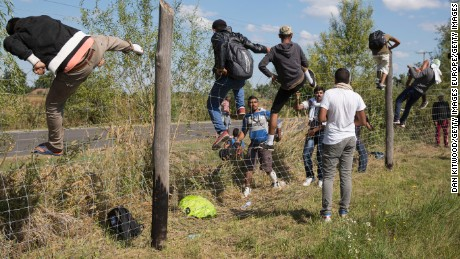 ROSZKE, HUNGARY - SEPTEMBER 09:  Migrants climb over fences after running from a collection point that had been set up to transport people to camps on September 9, 2015 in Morahalom, Hungary. People became impatient at the lack of imformation, facilities and transport to the camps and decided to storm past police lines making their way in all directions. Thousands of migrants have continued to cross into Hungary over the last few days from Serbia. Since the beginning of 2015 the number of migrants using the so-called 'Balkans route' has exploded with migrants arriving in Greece from Turkey and then travelling on through Macedonia and Serbia before entering the EU via Hungary. The number of people leaving their homes in war torn countries such as Syria, marks the largest migration of people since World War II.  (Photo by Dan Kitwood/Getty Images)