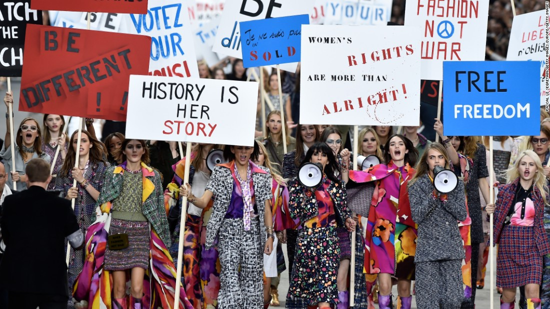 "Swapping out the usual front row seats with benches, attendees witnessed Cara Delevingne lead an army of models through the ""streets"" of Paris, holding inspirational quotes on signs as props."