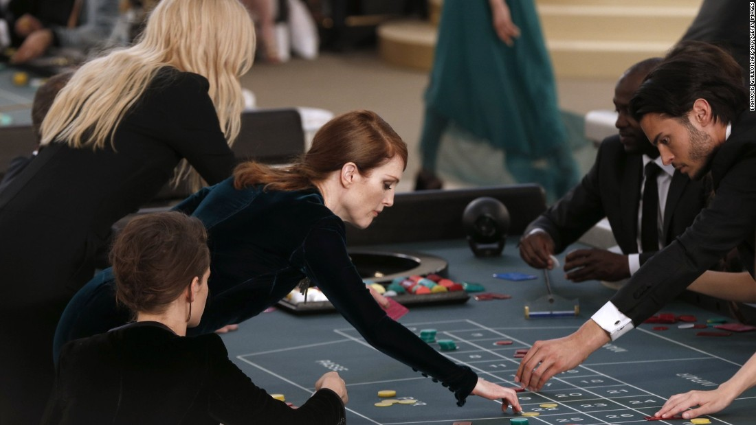 Hollywood starlets Kristen Stewart, Julianne Moore and Rita Ora opened for the show by taking center stage at casino tables. They then proceeded to play while models showed off the collection using the runway around them.