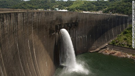 Flood gates on the Kariba Dam wall between Zimbabwe and Zambia open ceremonially on February 20, 2015 after the two neighbors signed $294 million in deals with international investors. The overhaul project of the world's largest man-made dam will fix deformities and cracks in walls that were discovered in a series of assessments. Those threaten to cause the massive structure to collapse -- an eventuality that would carry unimaginable humanitarian and environmental consequences if water in the 181 billion cubic metre capacity reservoir were freed by a massive breach. Given the high stakes involved, the European Union, World Bank, African Development Bank and the Swedish government agreed to bankroll the critical renovation effort.    AFP PHOTO / JEKESAI NJIKIZANA        (Photo credit should read JEKESAI NJIKIZANA/AFP/Getty Images)