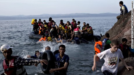 Migrants arrive on the shores of the Greek island of Lesbos after crossing the Aegean Sea from Turkey on a dinghy on September 9, 2015. The EU unveiled plans to take 160,000 refugees from overstretched border states, as the United States said it would accept more Syrians to ease the pressure from the worst migration crisis since World War II. AFP PHOTO / ANGELOS TZORTZINIS        (Photo credit should read ANGELOS TZORTZINIS/AFP/Getty Images)