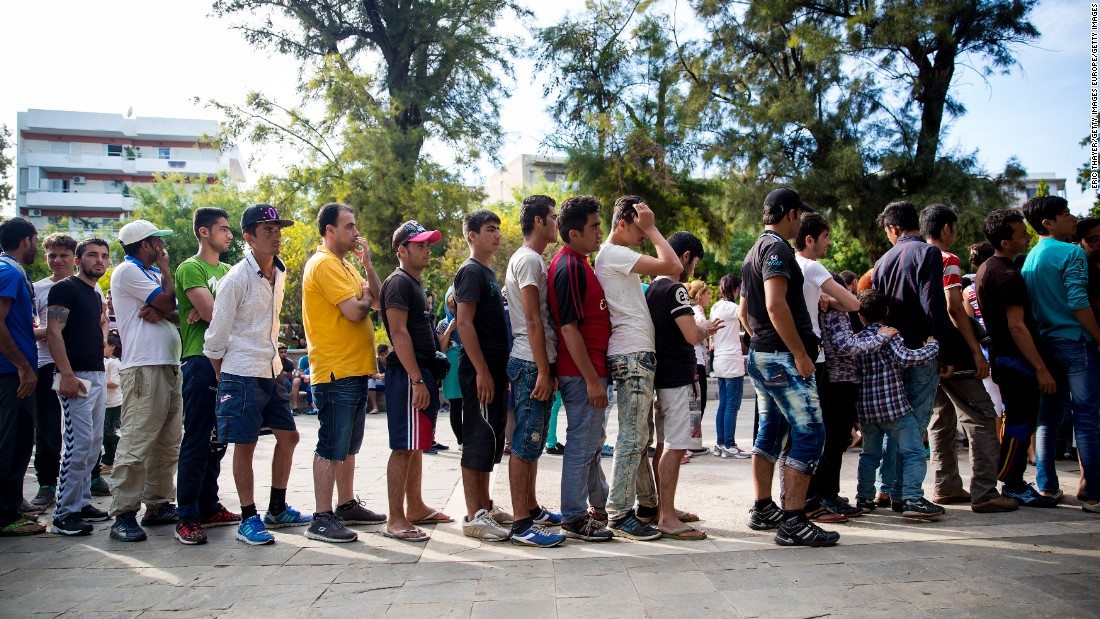 Long queues form as refugees wait to receive food in a park near the port of Mytilini, Lesbos. Many arrive wet, hungry and tired after paying huge amounts of money to risk their lives on small, crowded boats.