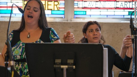 "Danielle Quaglia (left), a 30-year-old who's attended Saint Charles Borromeo her whole life, sings the Lord's Prayer with a Spanish choir group she's just joined. ""I love to sing...to share my talent that God gave me, hopefully to inspire others and make others feel welcome,"" she says."
