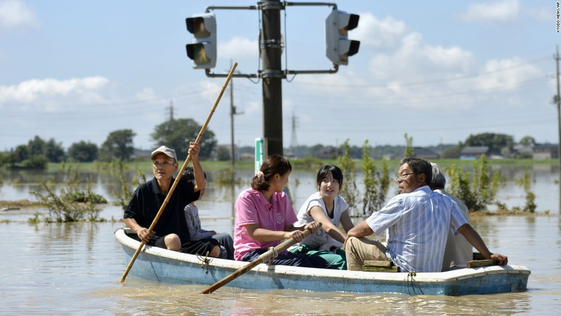 People paddle a boat on a flooded road in Joso, Japan, on Friday, September 11. The sun came out a day after floods washed away houses and forced people to rooftops waiting for rescue.