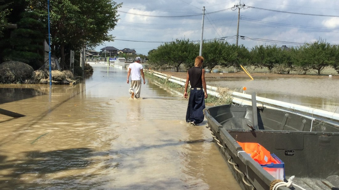 Men walk along a flooded road near Joso City, Japan on September 12.