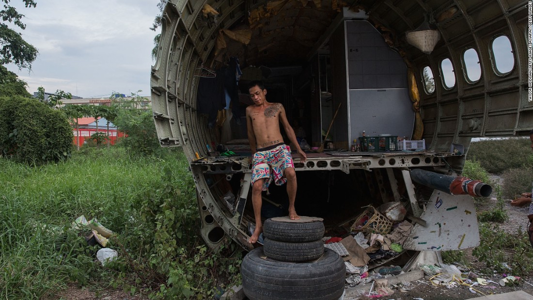 Unable to make enough money to rent a home, three Thai families apparently live in the field's disused airplanes.
