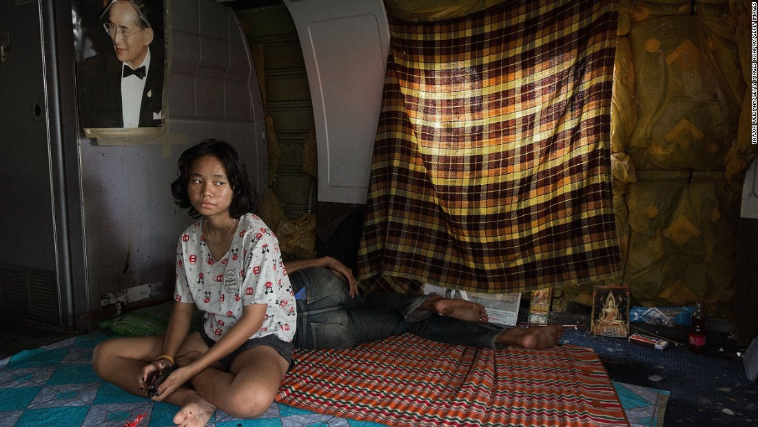 The interior of the planes occupied by the families show a few rudimentary decorations. Here a young woman sits under a picture of the Thai king, while makeshift curtains cover the windows.