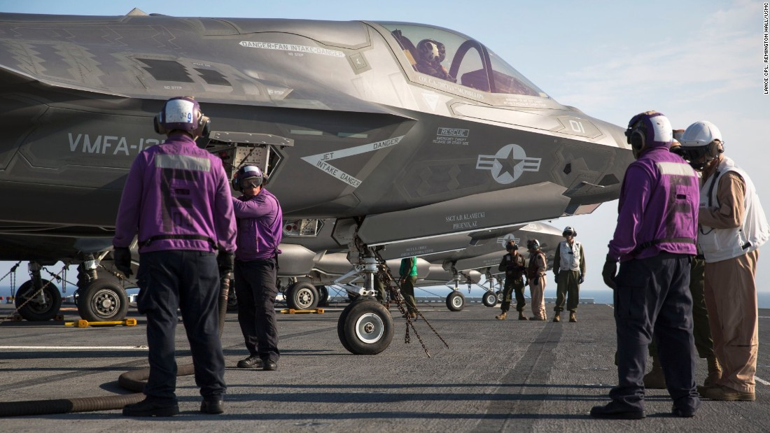 Marines and sailors aboard the amphibious assault ship USS Wasp secure and refuel an F-35B Lightning II fighter after its arrival for the first session of operational testing.