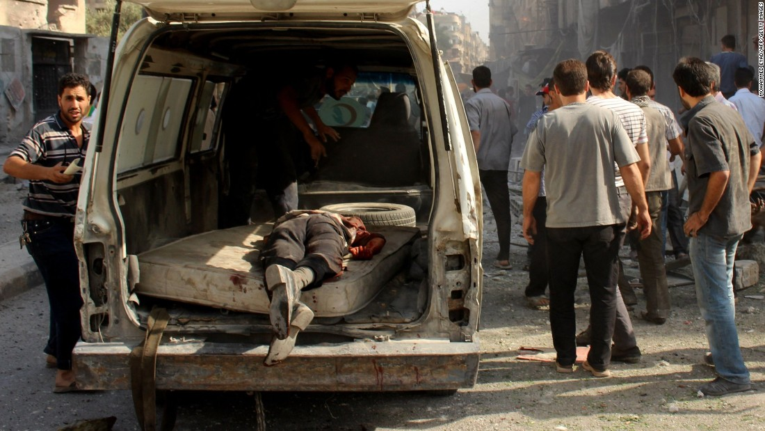 A man's body lies in the back of van as people search for the injured after airstrikes allegedly by the Syrian government on a market in a rebel-held Eastern Ghouta town on August 31, 2015.