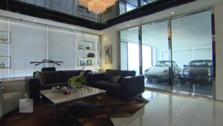 Two parked cars in overlook the living area of a Hamilton Scotts apartment.
