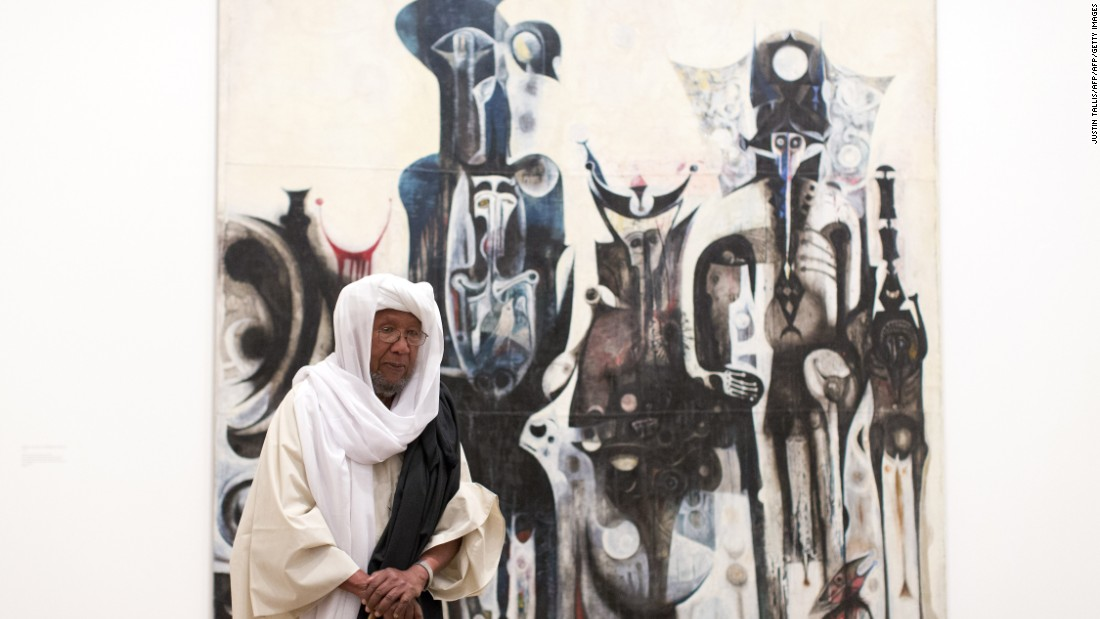 "Sudanese artist Ibrahim El-Salahi poses for a photograph in front of his painting entitled ""Reborn Sounds of Childhood Dreams"" at the Tate Modern in London."