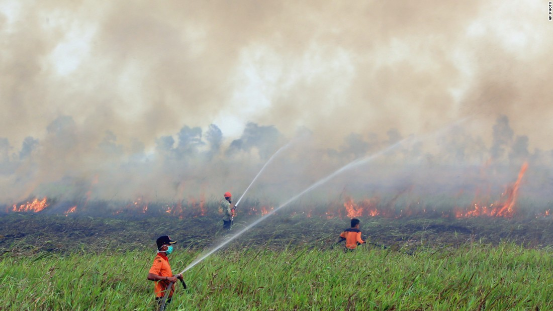 Firemen spray water to contain smoke-belching fires in Ogan Ilir, South Sumatra, Indonesia on September 5, 2015.