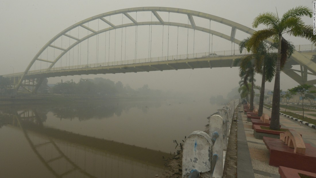 Cars drive through a bridge over the Siak river in Riau, Indonesia, on September 13, 2015. Indonesia declared a state of emergency in Sumatra's Riau province on September 14 as air quality hit a very dangerous level with an API exceeding 900.