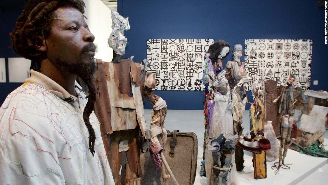 "Nigerian artist Dilomprizulike poses near one of his pieces of art,  ""Waiting for Bus' (2003), at the Centre Pompidou in Paris."