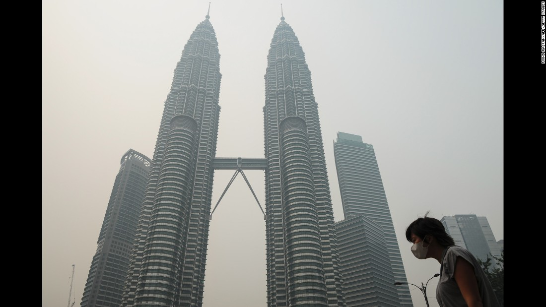 A woman wears a mask as haze shrouds the Petronas Twin Towers in Kuala Lumpur, Malaysia, on Friday, September 11.