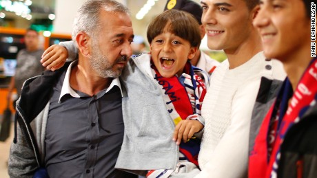 Syrian Osama Abdul Mohsen, left, holds his son Zaid as they arrive at the Barcelona train station on Wednesday, Sept.16, 2015. The Syrian refugee tripped at a border hotspot by a Hungarian journalist in an incident captured on video that generated global outrage will live in a Madrid suburb after a Spanish soccer academy convinced him to take an apartment offer and help to rebuild his life, an official with the school said Wednesday. Osama Abdul Mohsen was on a train expected to arrive in Madrid at midnight Wednesday. (AP Photo/Manu Fernandez)