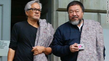 Artists Anish Kapoor, left, and Ai Weiwei  carry blankets as they set off from The Royal Academy of Arts to walk across London in support of refugees, Thursday, Sept. 17, 2015. They carried a single blanket as a symbol of the need that faces 60 million refugees in our world today. The artists will repeat this action in cities across the world over the next few months. (AP Photo/Kirsty Wigglesworth)