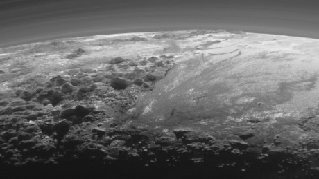 Just 15 minutes after its closest approach to Pluto on July 14, 2015, NASA's New Horizons spacecraft looked back toward the sun and captured a near-sunset view of the rugged, icy mountains and flat ice plains extending to Pluto's horizon. The smooth expanse of the informally named Sputnik Planum (right) is flanked to the west (left) by rugged mountains up to 11,000 feet (3,500 meters) high, including the informally named Norgay Montes in the foreground and Hillary Montes on the skyline. The backlighting highlights more than a dozen layers of haze in Pluto's tenuous but distended atmosphere. The image was taken from a distance of 11,000 miles (18,000 kilometers) to Pluto; the scene is 230 miles (380 kilometers) across.