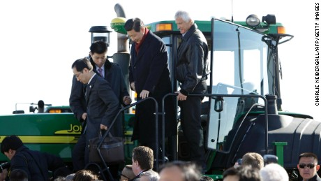 President Xi Jinping (2nd R) climbs out of the cab of a tractor a farm  in Maxwell, Iowa on February 16, 2012. s)