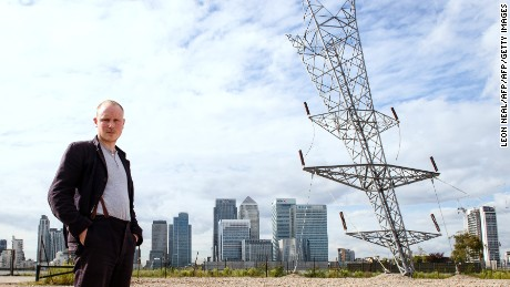 "British artist Alex Chinneck poses in front of his latest sculpture ""A bullet from a shooting star"" on the Greenwich Peninsula in London on September 17, 2015. The 35-metre tall, upside-down electricity pylon overlooks the Canary Wharf financial district. AFP PHOTO / LEON NEAL = RESTRICTED TO EDITORIAL USE, MANDATORY MENTION OF THE ARTIST UPON PUBLICATION, TO ILLUSTRATE THE EVENT AS SPECIFIED IN THE CAPTION =        (Photo credit should read LEON NEAL/AFP/Getty Images)"