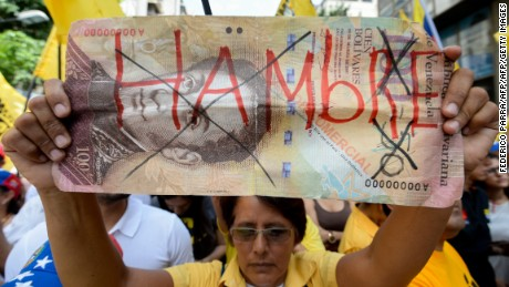 "An activist of Venezuela's opposition holds a fake bill reading ""Hunger"" during a demonstration in Caracas against the gouverment of Nicolas Maduro, on September 19, 2015. AFP PHOTO / FEDERICO PARRA        (Photo credit should read FEDERICO PARRA/AFP/Getty Images)"