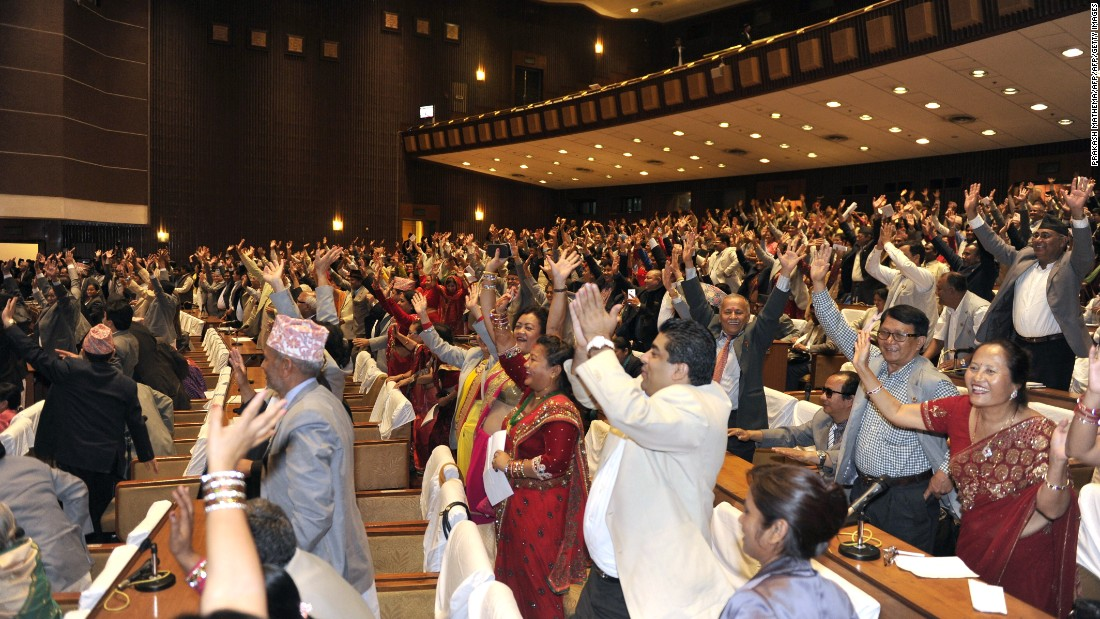 Nepalese lawmakers wave while Nepal's parliament passes a new national constitution in Kathmandu on September 16, 2015.