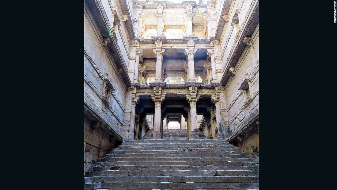 """This impressive, ignored, disintegrating stepwell is in a small village about 15 minutes away from its famous sister, Rudabai vav in Adalaj, and yet no-one ever visits. It was built at the same time, most likely by the same queen, and while less showy and grand it's nevertheless beautiful and elegant, with sculptural niches climbing up the narrow walls. It's ""protected"" by the local government (even though chunks are falling from it and bonfires have been lit within) but easily accessible through an adjacent temple."""