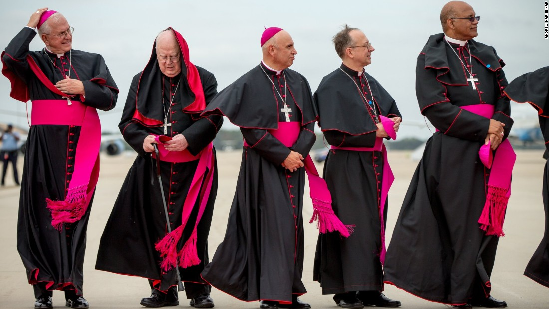 Clergy members brace for the wind as they stand on the tarmac at Andrews Air Force Base.