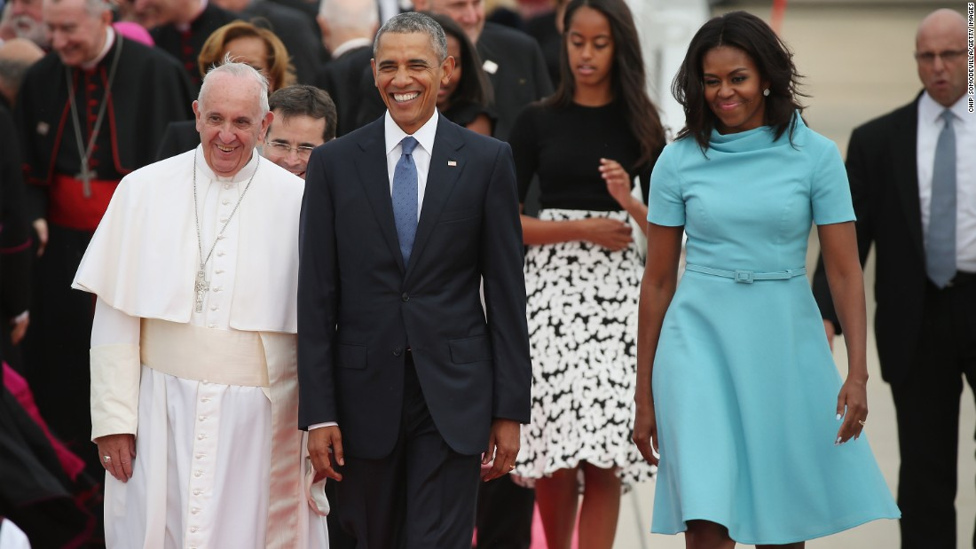 Pope Francis is escorted by the Obamas and their daughters after arriving in the country.