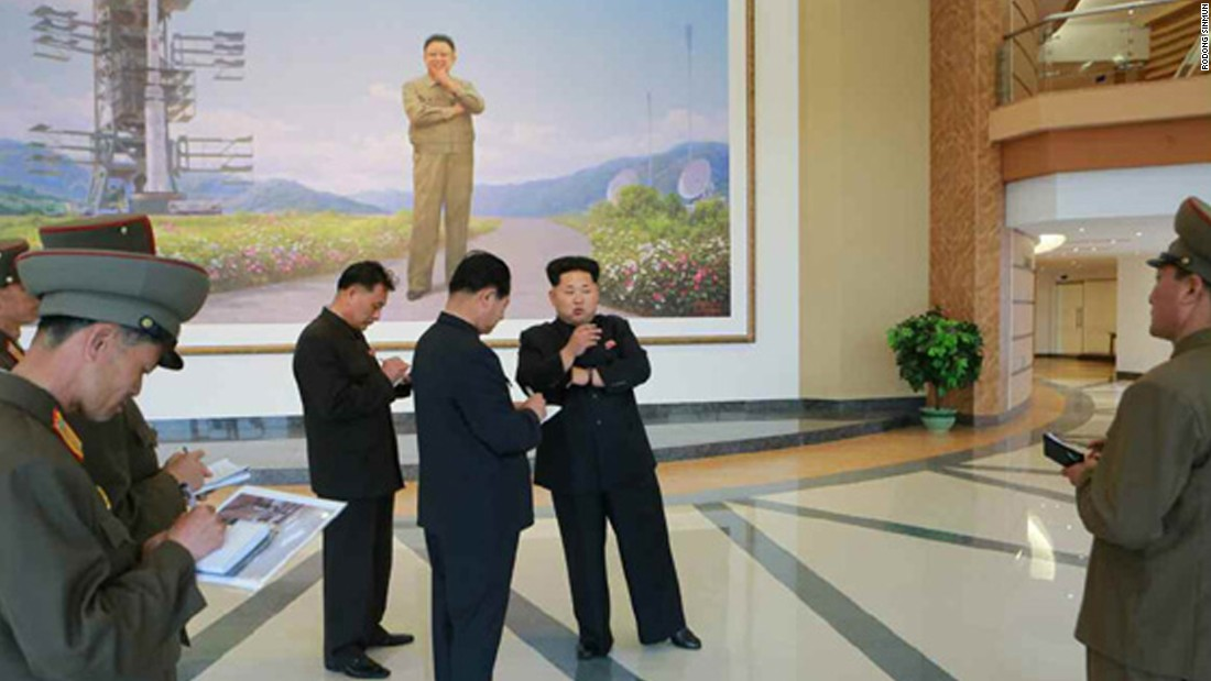 Kim Jong Un is pictured in front of a large painting of his father and former leader, Kim Jong Il, posing next to a satellite inside the satellite control center.