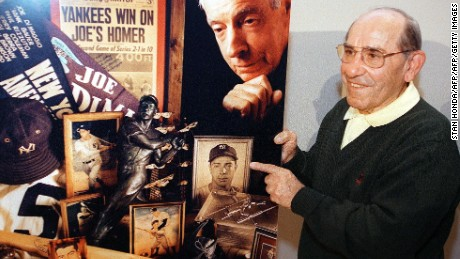 MONTCLAIR, :  Former New York Yankees catcher Yogi Berra holds a montage of photos of Yankees legend Joe DiMaggio at a press conference at the Yogi Berra Museum 08 March 1999 in Montclair, New Jersey. DiMaggio died earlier in the morning 08 March at his home in in Hollywood, Florida at the age of 84. Berra was a teammate and friend of DiMaggio. AFP PHOTO/Stan HONDA (Photo credit should read STAN HONDA/AFP/Getty Images)