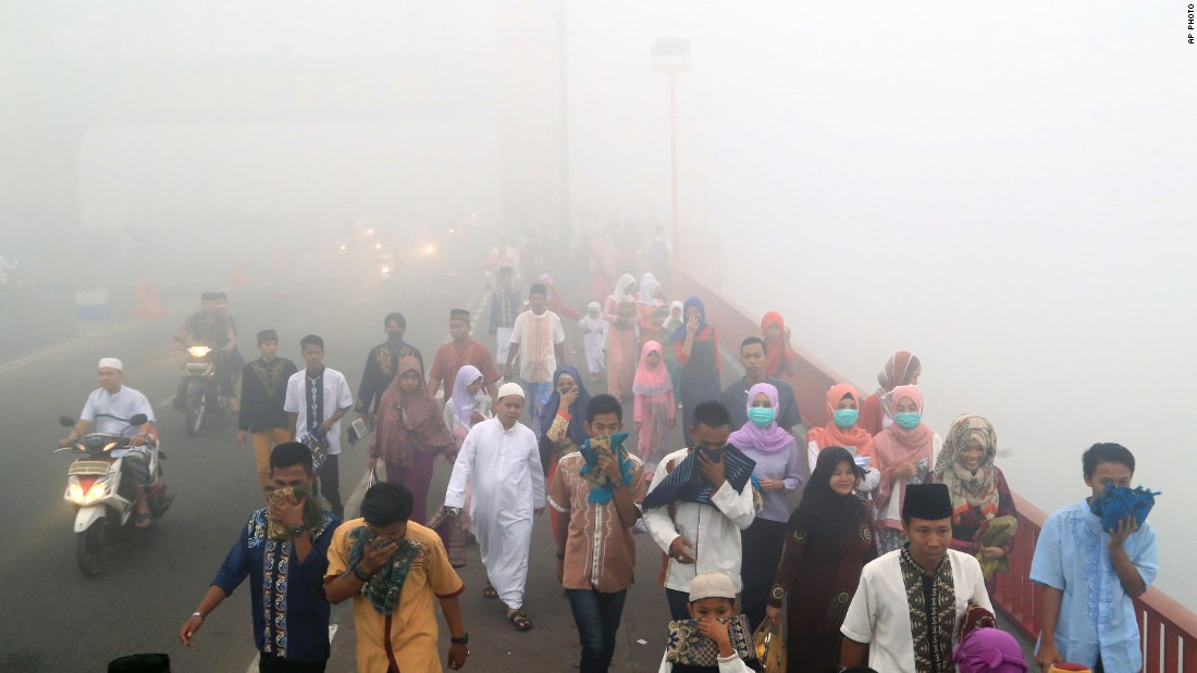"Indonesians cover their mouths and noses from the pollution as they travel to attend a morning prayer celebrating Eid al-Adha, or the ""Festival of Sacrifice,"" in Palembang, South Sumatra on September 24."