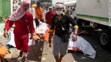 Saudi emergency personnel and Hajj pilgrims carry a wounded person at the site where at least 450 were killed and hundreds wounded in a stampede in Mina, near the holy city of Mecca, at the annual hajj in Saudi Arabia on September 24, 2015. The stampede, the second deadly accident to strike the pilgrims this year, broke out during the symbolic stoning of the devil ritual, the Saudi civil defence service said.