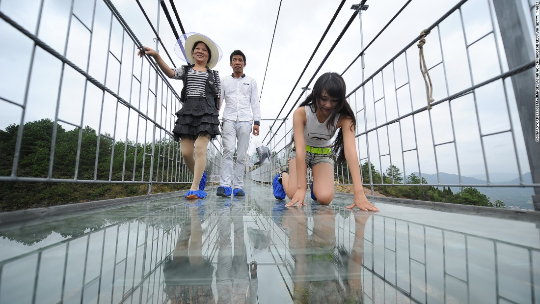 Tourists walk on a suspension bridge made of glass in China's Shiniuzhai National Geological Park in September 2015.