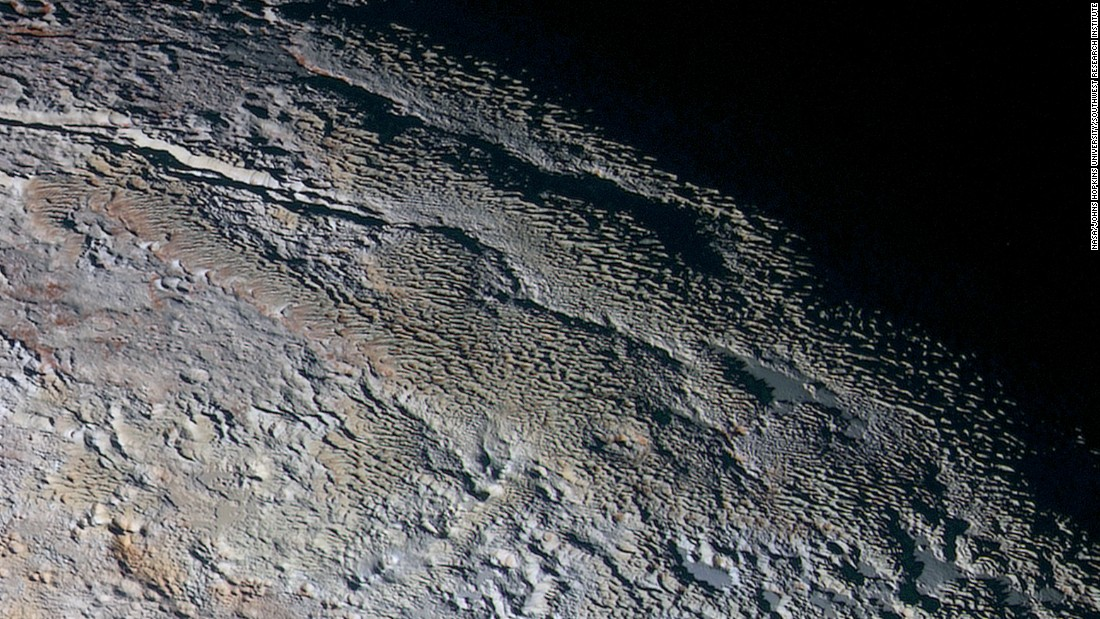 "These photos show Pluto's variety of textures, including what NASA calls ""rounded and bizarrely textured mountains."" The mountains are informally called the Tartarus Dorsa. This image shows about 330 miles (530 kilometers) of Pluto's terrain. It combines blue, red and infrared images taken by the space probe's Ralph/Multispectral Visual Imaging Camera. The images were taken on July 14, during the probe's flyby. They were released on September 24."