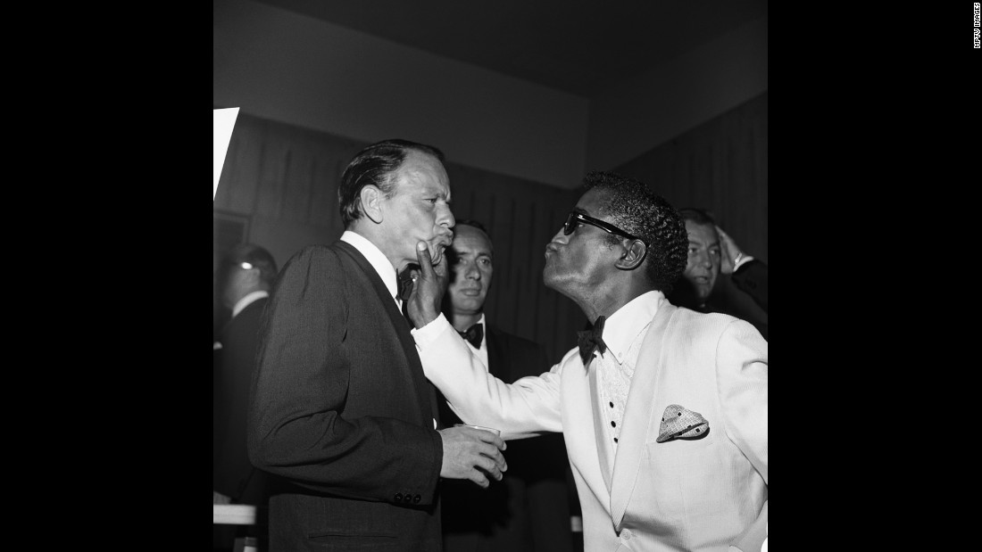 Davis squeezes Sinatra's face in 1961 while comedian Joey Bishop, center, looks on.