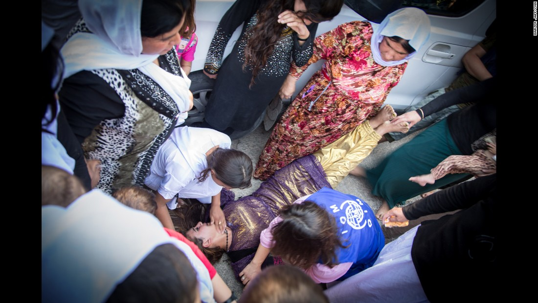 A Yazidi girl faints while saying goodbye to relatives who are going to Germany.
