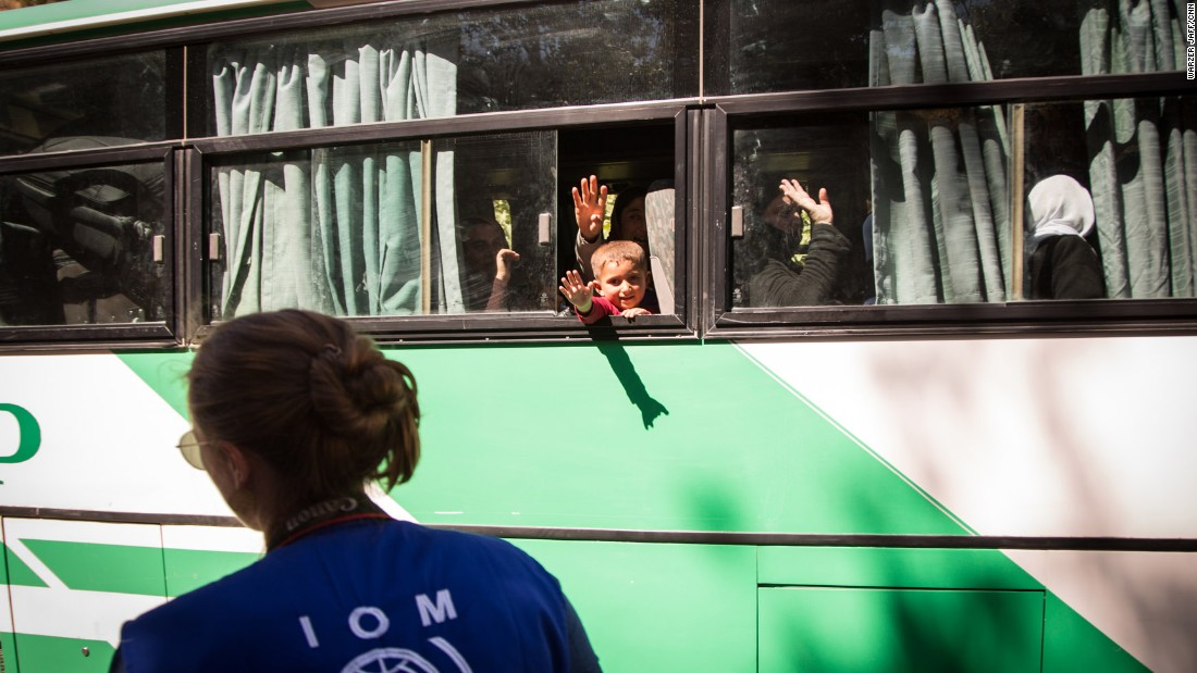 Women and children wave goodbye to relatives before their journey to Germany.