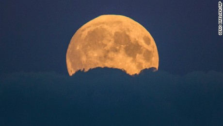 "A full moon rises between clouds in Berlin, Germany, Sunday, Sept. 27, 2015. The full moon was seen prior to a phenomenon called a ""Super Moon"" eclipse that will occur during moonset on Monday morning, Sept. 28. (AP Photo/Gero Breloer)"