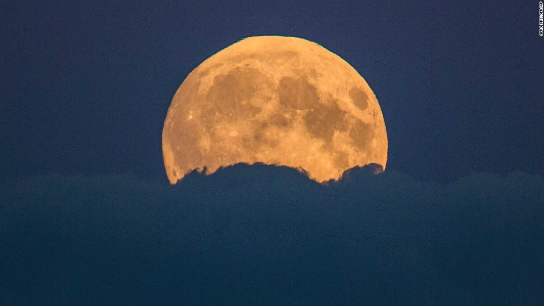 The supermoon rises from behind clouds in Berlin.