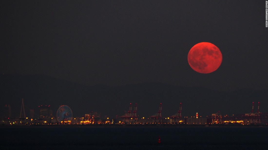 "<a href=""http://ireport.cnn.com/docs/DOC-1273405"">Dennis Doucet </a>captured the red supermoon rising above Osaka, Japan. In the background, you can make out the mountains of the Nara prefecture."