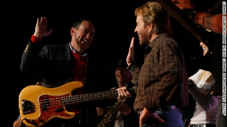 "Republican Presidential hopeful and former Arkansas Governor Mike Huckabee high-fives with actor Chuck Norris during a ""Chuck and Huck"" rally January 1, 2008 in Des Moines, Iowa."