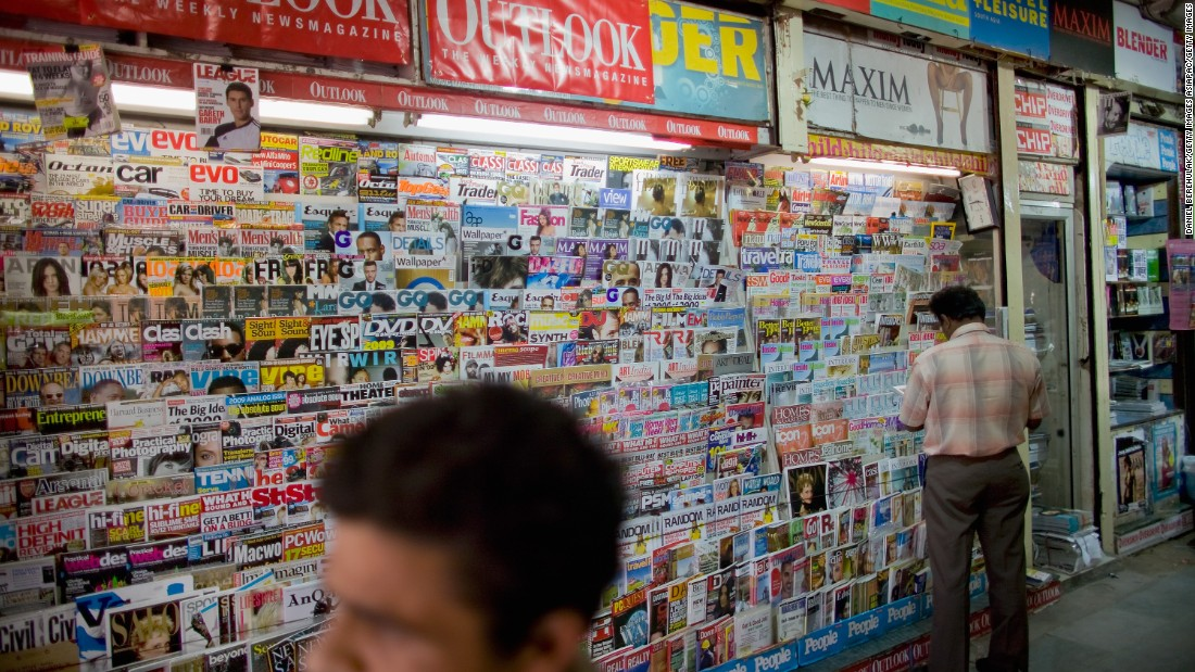 A customer looks at magazines at a newstand in Khan Market in New Delhi, India.