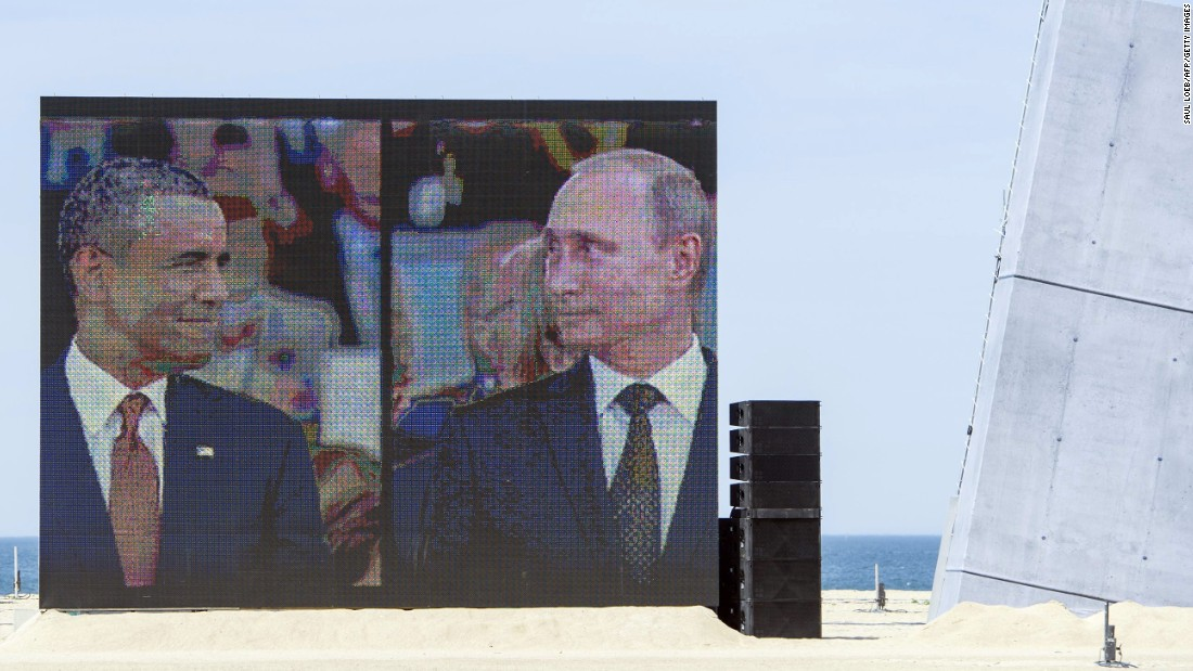 "Obama and Putin share a comical and awkward moment on a large split-screen during an international ceremony on the stretch code-named Sword Beach, in Ouistreham, France, to commemorate the Allied invasion of Normandy on June 6, 2014. Obama and Putin had an informal 15-minute chat during lunch at the ceremony that marked the 70th anniversary of the D-day landings. ""It's a positive thing that they spoke, but more needs to be done,"" a senior U.S. official said at the time."