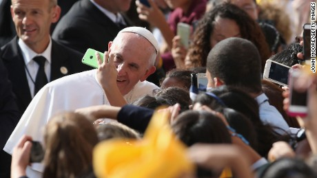 "NEW YORK, NY - SEPTEMBER 25:  School children take ""selfies"" with Pope Francis upon his arrival to the Lady Queen of Angels school on September 25, 2015 in New York City. The Pope visited the inner city Catholic school in east Harlem and met with children, immigrants and Catholic Charities workers on the second day of his visit to New York City.  (Photo by John Moore/Getty Images)"
