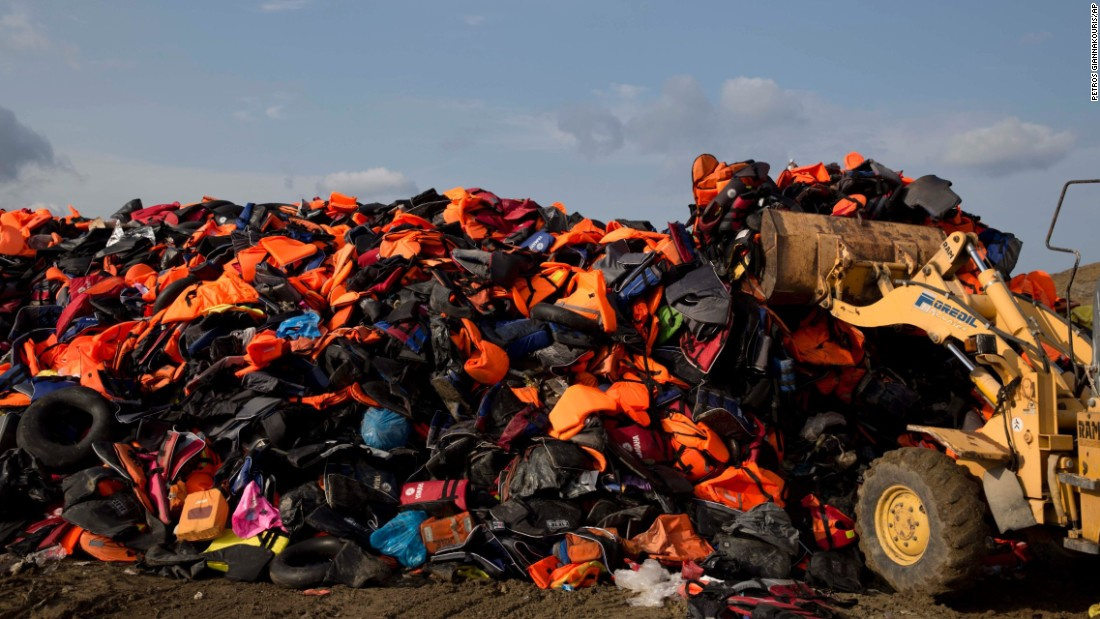 In September 2015, an excavator dumps life vests that were previously used by migrants on the Greek island of Lesbos.
