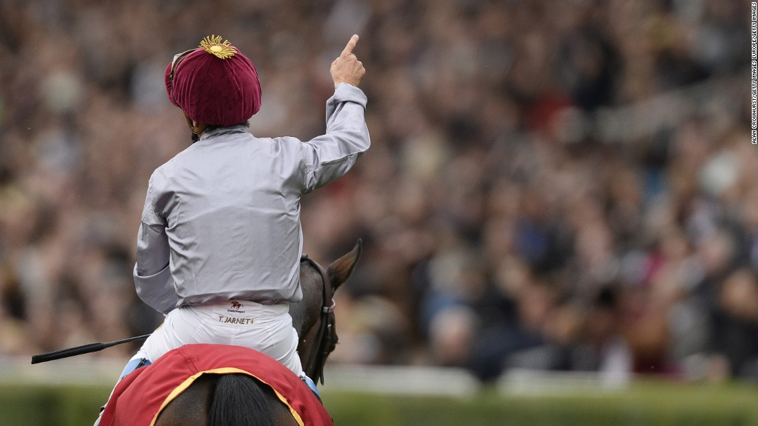 Thierry Jarnet salutes the win in front of 50,000-strong crowd at Paris' Longchamp racecourse last year. The French jockey will be piloting Treve again in this year's race.