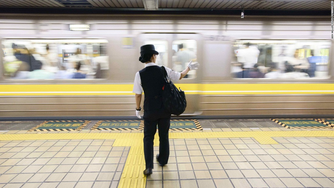 A train conductor signals a clear subway platform to a colleague. Nagoya is home to the SCMaglev and Railway Park, a railway museum where train lovers can get a hands-on look at the impressive collection.