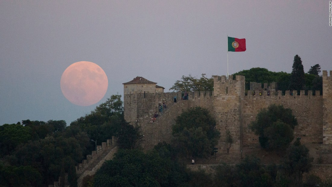 "A <a href=""http://www.cnn.com/2015/09/24/us/supermoon-eclipse-blood-moon-sunday-feat/"" target=""_blank"">""super moon""</a> rises behind St. George's Castle in Lisbon. A super moon is a full moon that appears larger because it's at perigee, the closest point of its orbit with Earth."
